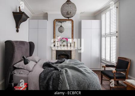 Lit rembourré de luxe de sofa.com dans chambre avec cheminée d'origine, et la culpabilité de stockage intégré miroir Banque D'Images