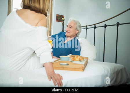 Couple having breakfast in bed, smiling Banque D'Images