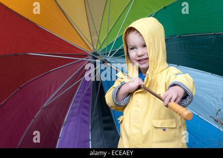 Garçon dans un manteau de pluie multicolores holding umbrella Banque D'Images