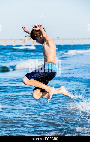 Garçon roux sur la plage de sauter dans les vagues Banque D'Images