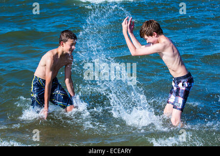 Deux garçons les projections d'eau dans l'océan Banque D'Images