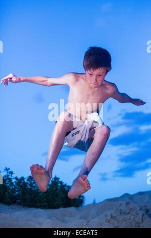Garçon roux sur la plage de sauter en l'air Banque D'Images