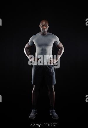 Full Length portrait of muscular young man in sportswear looking at camera sur fond noir. L'Afrique de l'athlète. Banque D'Images