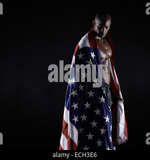 L'athlète masculin un drapeau américain sur fond noir. Studio shot of muscular sportsman avec USA flag. Jeune homme Banque D'Images