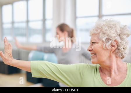 Close-up shot of woman doing stretching entraînement à la classe de yoga. Les femmes pratiquant le yoga au club Banque D'Images