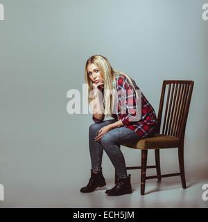 Portrait de jeune femme en tenue décontractée assis sur une chaise en regardant la caméra. Modèle des femmes de Banque D'Images