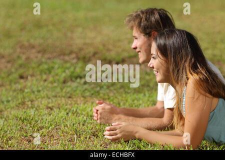 Profil d'un couple couché dans l'herbe et à la voiture avec un fond vert Banque D'Images