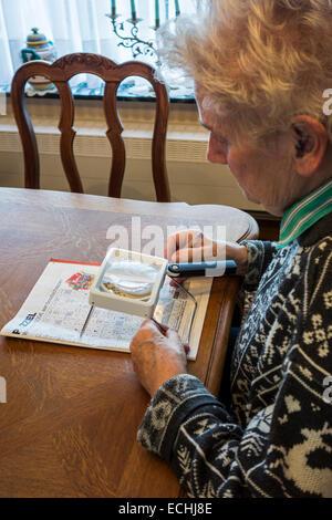 Femme âgée souffrant de presbytie myopie / / manque de vision à la recherche de mots croisés par loupe Banque D'Images