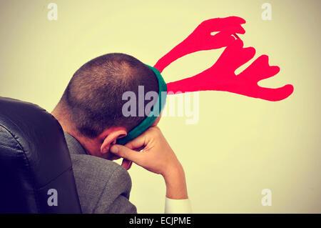 Un homme avec un bandeau reindeer antlers se détendre dans son bureau de président après un party de Noël de bureau, avec un effet de filtre