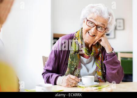 Happy senior woman looking at ami tandis que le café au petit-déjeuner table en maison de soins infirmiers Banque D'Images
