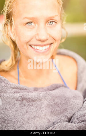 Portrait of smiling young woman wrapped in towel outdoors Banque D'Images
