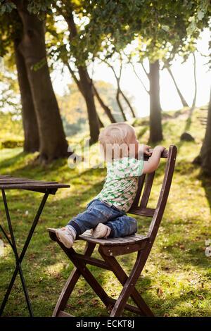 Toute la longueur de baby boy sitting on wooden chair in park Banque D'Images