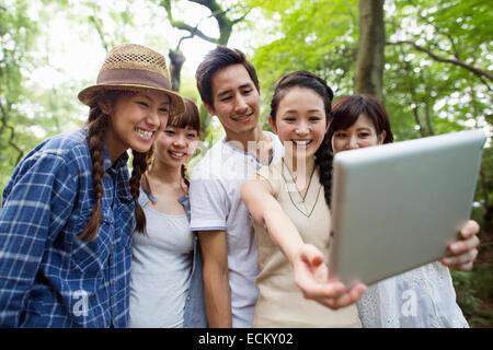 Groupe d'amis à une fête en plein air dans une forêt. Banque D'Images