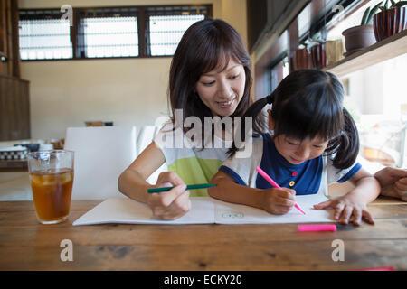 La mère et la fille assis à une table, dessin avec feutres, souriant. Banque D'Images