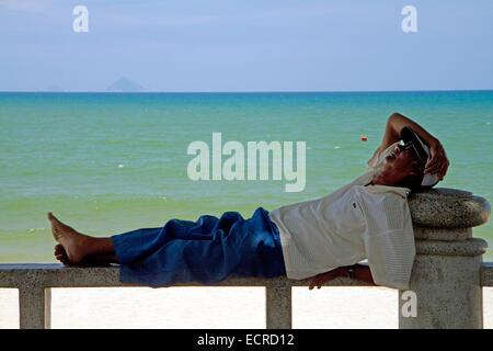 L'homme de prendre une sieste sur un banc sur la plage de Nha Trang, Vietnam. Banque D'Images
