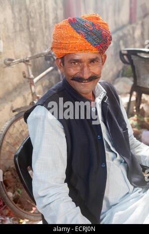 Homme portant un turban Rajasthani traditionnelle avec un grand sourire et une grande moustache assis dans sa cour, Banque D'Images