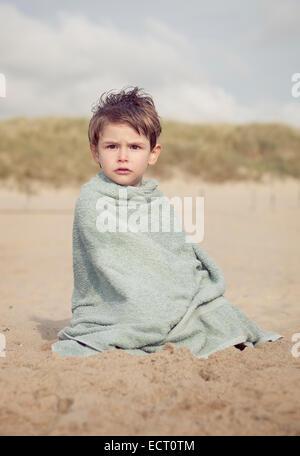 Petit garçon assis sur la plage en cours de chauffage dans une serviette Banque D'Images