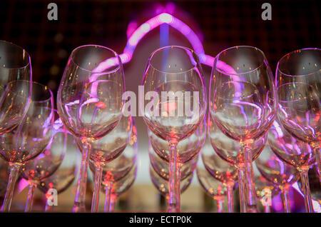 Verres à vin alignés sur un bar en face d'un éclairage au néon. Banque D'Images