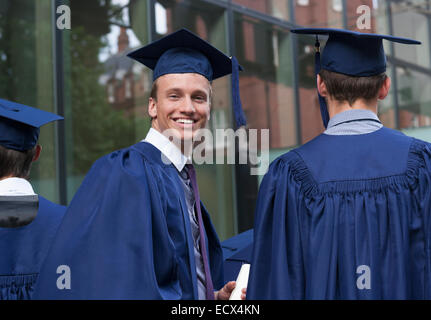 Smiling university student looking over Shoulder at camera sur le campus Banque D'Images