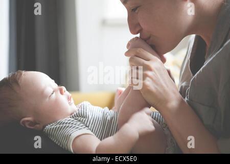 Mother holding et d'embrasser les pieds du bébé peu Banque D'Images