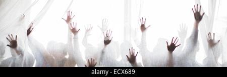 Silhouette de gens qui élèvent les mains derrière le rideau transparent Banque D'Images