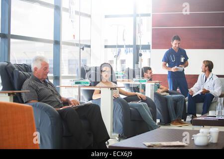 Les patients qui suivent un traitement médical avec les médecins discutant en clinique externe Banque D'Images