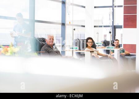 Trois patients assis dans des fauteuils, en traitement médical en clinique externe Banque D'Images