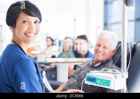 Portrait of smiling doctor aider patient sous traitement médical en clinique externe Banque D'Images