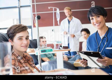 Smiling doctors contrôler avec les patients qui suivent un traitement médical en clinique externe Banque D'Images