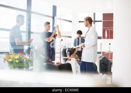 Les médecins s'occuper des patients qui suivent un traitement médical en clinique externe Banque D'Images