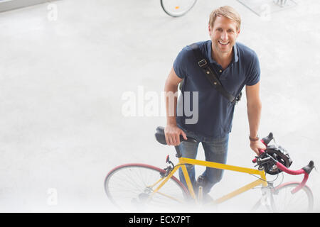 Smiling man standing with bicycle