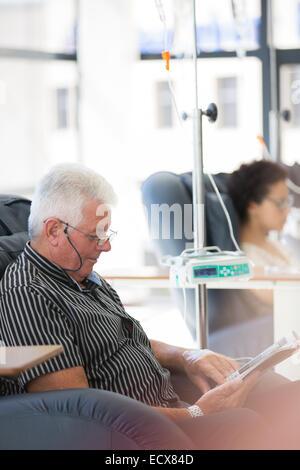 Man reading magazine, en traitement médical en clinique externe Banque D'Images