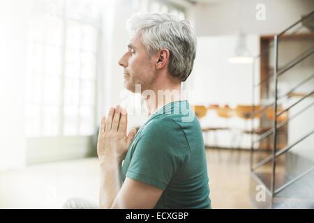 Vieil homme méditant à l'intérieur Banque D'Images