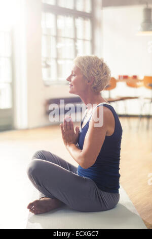 Older woman sitting on exercise mat Banque D'Images