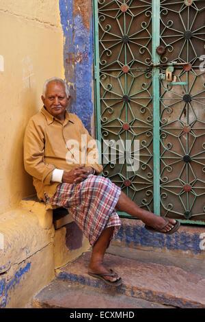 Vieil homme assis devant son domicile dans la ville bleue, Jodhpur, Rajasthan, India Banque D'Images
