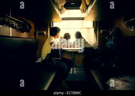 Le père et les enfants à la fenêtre de la remorque à Banque D'Images
