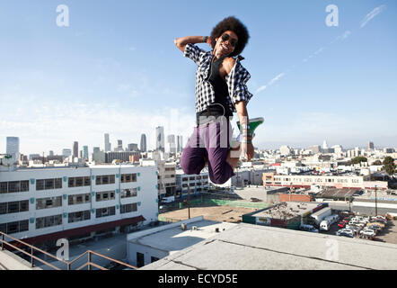 African American man jumping for joy on urban rooftop Banque D'Images
