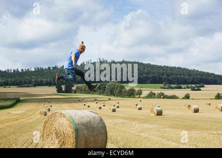 Farmer sautant hay bale in field Banque D'Images