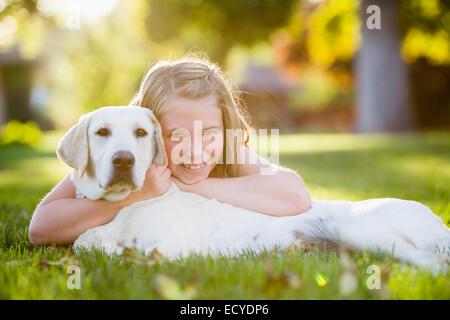 Caucasian girl hugging dog pet sur pelouse Banque D'Images