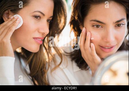 Les femmes hispaniques miroir en appliquant le maquillage Banque D'Images