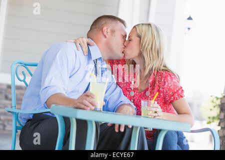Caucasian couple kissing on porch Banque D'Images