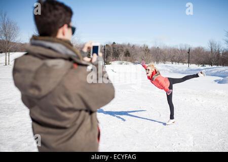 Caucasian man taking picture of girlfriend patinage sur lac gelé Banque D'Images