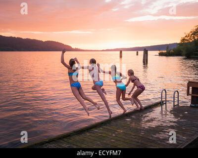 Les filles de sauter dans le lac à partir de dock en bois Banque D'Images