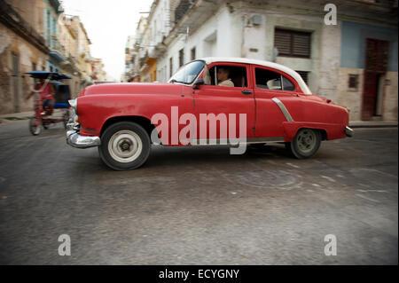 La HAVANE, CUBA - 12 juin 2011: American Classic voiture taxi drives passé un vélo taxi à un interesection dans le centre de La Havane.