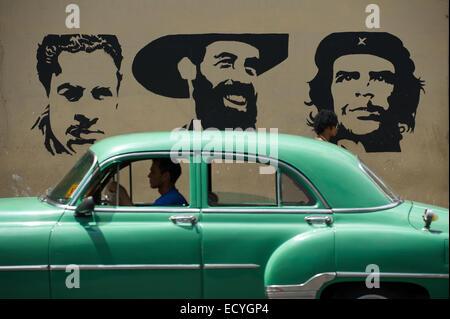 La HAVANE, CUBA - le 13 juin 2011: les lecteurs de voiture américaine classique passé avec panneau pochoir Mella, Cienfuego, et Guevara.