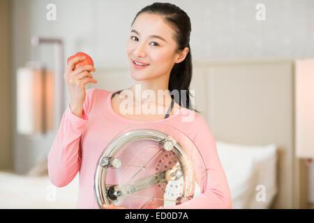 Happy young woman holding apple et l'échelle de poids Banque D'Images