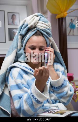 Fille en robe de chambre à parler sur son téléphone portable tout en regardant ses ongles Banque D'Images