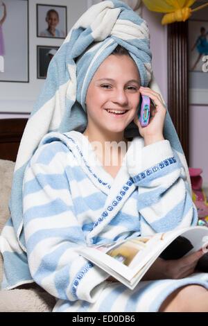 Fille en robe de chambre parlant au téléphone lors de la lecture de magazine Banque D'Images