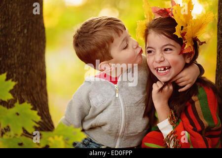 Boy hugging une fille, en essayant de l'embrasser Banque D'Images