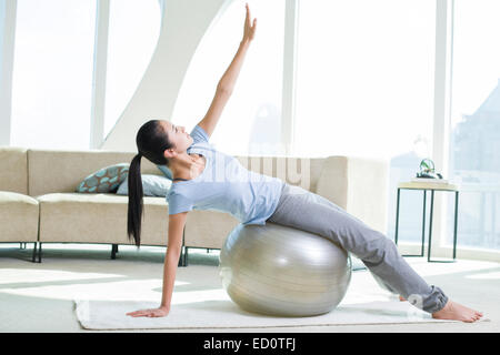 Young woman practicing yoga avec fitness ball Banque D'Images